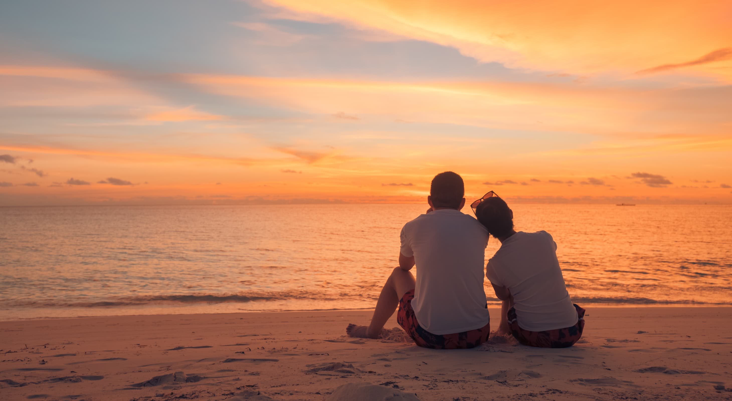 Couple sitting on a beach watching the sunset
