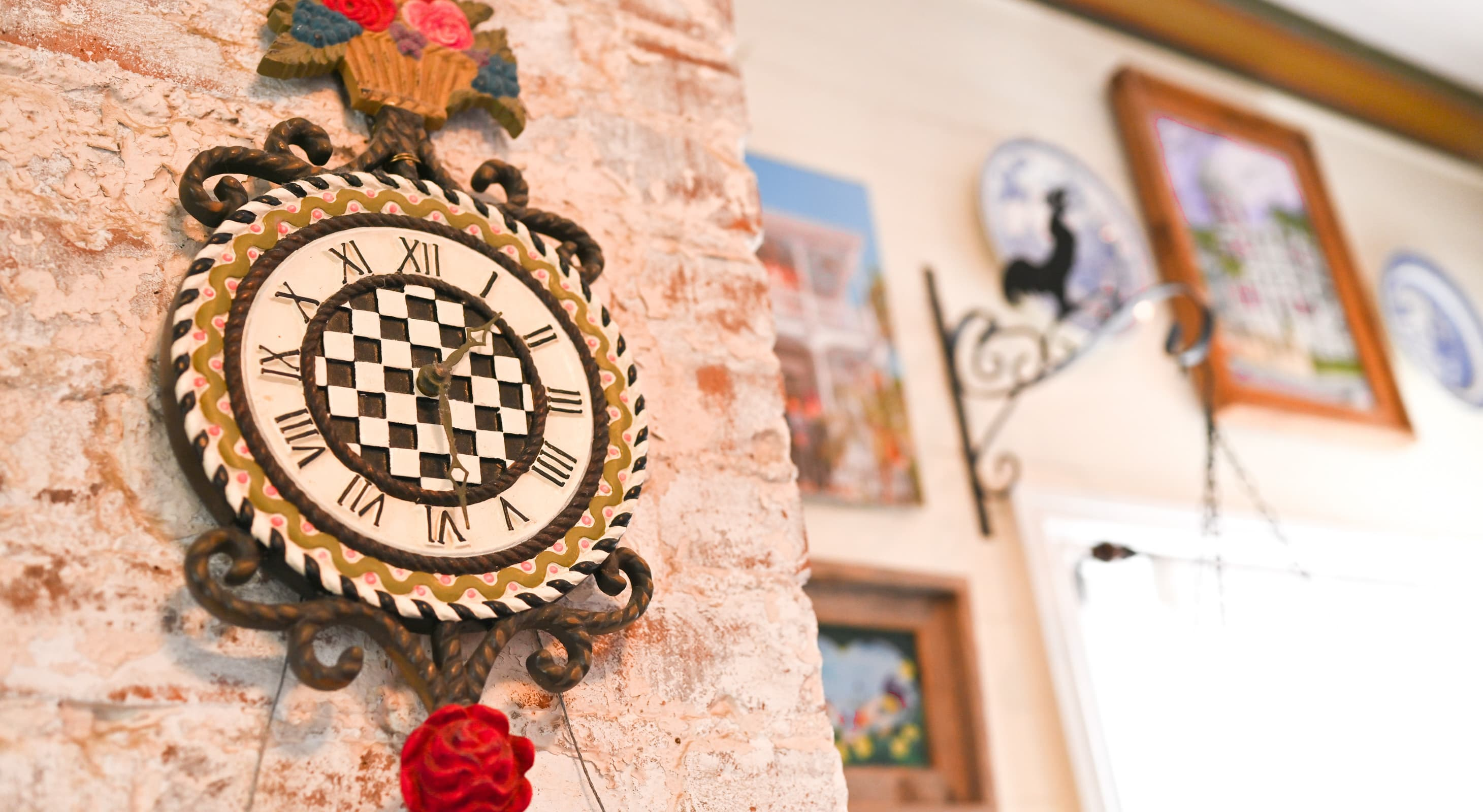 Wall clock with paintings on a wall in the background